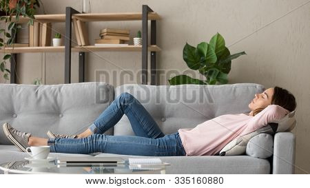 Tired Young Woman Relax At Home Sleeping On Cozy Couch
