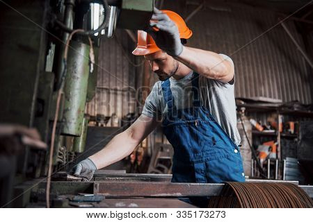 Portrait Of A Young Worker In A Hard Hat At A Large Metalworking Plant. The Engineer Serves The Mach