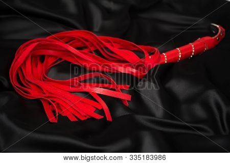 Red Whip On A Black Silk Background. Accessories For Adult Sexual Games. Toys For Bdsm.