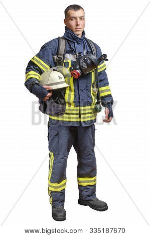 A Young Brave Fireman In A Fireproof Uniform Stands And Looks At The Camera With A Helmet In His Han