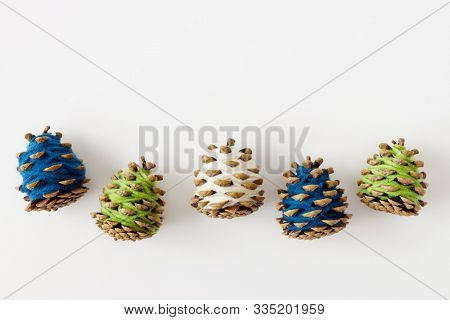 Pinecones Wrapped In Colorful Yarn. A simple holiday craft.