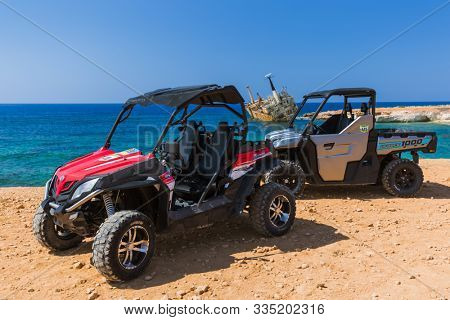 Paphos, Cyprus - September 29, 2019: Buggy excursion on the shore of a bay with old ship.