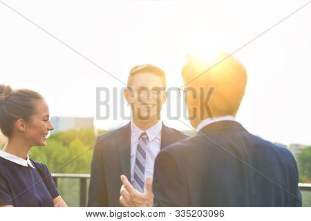 Mature businessman discussing plans with colleague in office rooftop with yellow lens fare