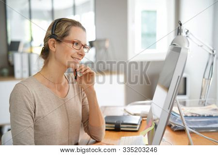 young business woman on the phone in an office