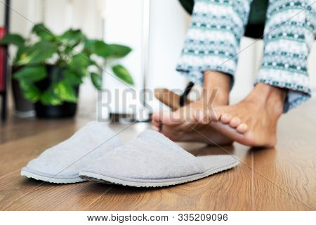 closeup of a man in pajamas sitting on a modern rocker about to put on a pair of gray slippers placed on the laminate floor in the foreground