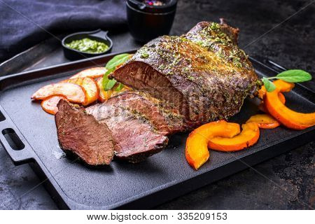 Traditional roasted beef heart with fried pumpkin slices and chimichurri sauce as closeup on a modern design cast iron tray