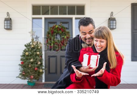 Young Mixed Race Couple Exchanging Gift On Front Porch of House with Christmas Decorations.