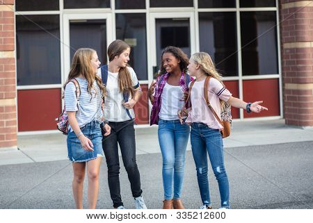 Candid photo of a group of teenage girls socializing, laughing and talking together at school. A multi-ethnic group of real junior high aged students walking outside a school building