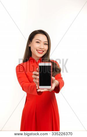 Young Asian Woman In Ao Dai Showing Blank Smartphone Screen Over White Background