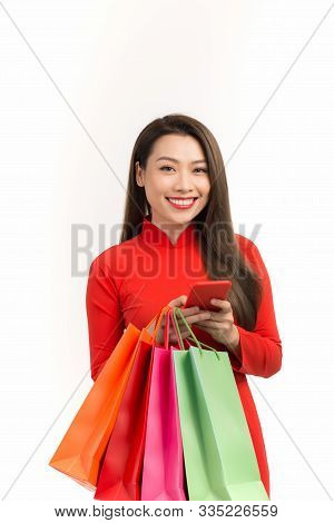 Vietnamese Girl In Dress Traditional Ao Dai Using Smartphone To Shopping Online For Lunar New Year