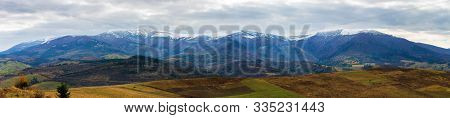 Borzhava Mountain Ridge With Snow Capped Tops. Beautiful Countryside Landscape On An Overcast Novemb