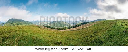 Agricultural Grassy Field On Hillside In Mountains Near Village. Beautiful Rural Landscape With Hill