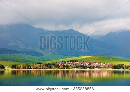 Village On The Shore Of A Lake. Beautiful Rural Landscape In Mountains. Distant Snow Covered Peaks I
