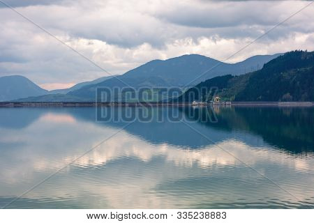Liptovska Mara Lake In The Evening. Cloudy Springtime Weather Above The Distant Mountains Reflecting