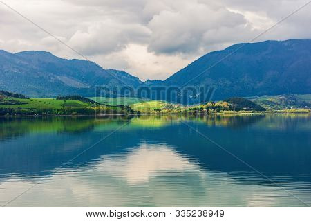 Village On The Shore Of A Lake. Beautiful Landscape In Mountains. Distant Peaks In Clouds. Amazing S