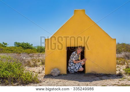 Dutch Woman Entering Yellow Slave House At The Beach Of Bonaire