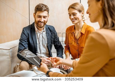 Young Couple Talking With A Sales Manager Or Real Estate Agent, Offering Some Products With A Digita
