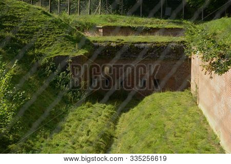 Old Abandoned Fortress In Focus Behind Defocused Fence, Desolated Area Behind Fence