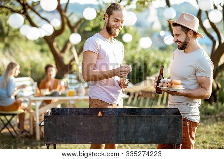 Two Male Friends Cooking Food On A Barbecue In The Beautiful Garden During Festive Lunch With Girlfr