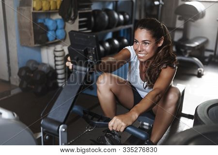Side-shot Attractive Motivated Young Hispanic Sportswoman Using Leg Press, Workout On Functional Tra