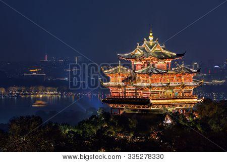 Night view of illuminated Cheng Huang Ge (City God Pavillion) with West Lake and city skyline on background, Hangzhou, China