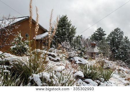 Winter Scene With Snow On Buildings, Trees, Plants, And Rocks