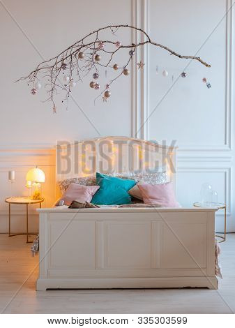 White Cozy Modern Bedroom With Festive Decor. Wood Bed In Scandinavian Style With A Wooden Stick In