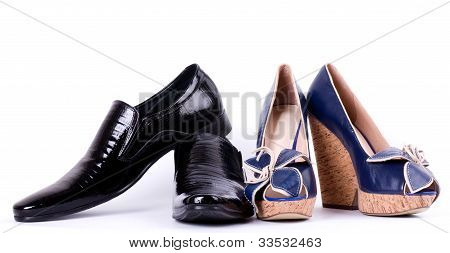 Sexy fashionable man's and womanish shoes on white background.
