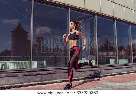 Beautiful Dynamic Sporty Girl Runs On Jog In Morning, Lifestyle Motivation In Summer In City. Sports