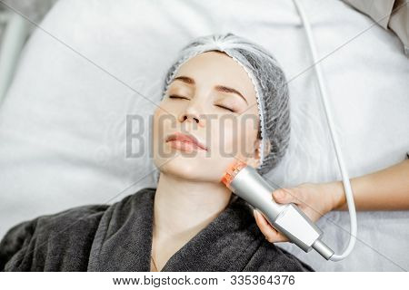 Woman during the oxygen mesotherapy procedure at the beauty salon, close-up view. Concept of a professional facial treatment poster
