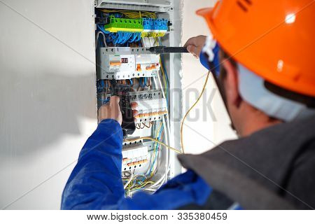 Electrician Testing The Electrical Shield. Electrical Switchboard With Automats And Wires.