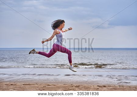 Young Woman With Black Hair Jumps While Jogging. A Woman Is Engaged In Gymnastics In The Spring Morn