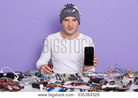 Image Of Confident Professional Radiotrician Sitting At His Workplace, Holding Smartphone And Side C