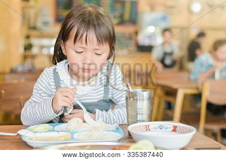 Little Asian Child Girl With Unhappy Face While Having Lunch On Table In Restaurant, Picky Eater Don