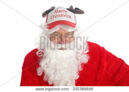 Santa Claus wears a Reindeer Antler Hat. Santa sits and models his Ball hat complete with antlers. Isolated on white with room for text. Merry Christmas to all.