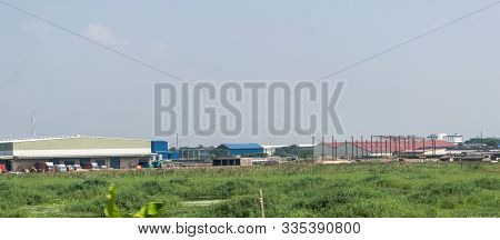 Industrial Area Landscape. Industry Surrounded By Rural Agricultural Field And Green Summer Meadow.