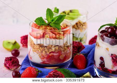 Healthy Dessert With Cherries, Strawberries, Kiwi, Cream Cheese Ricotta, Granola, Mint In Glass On B