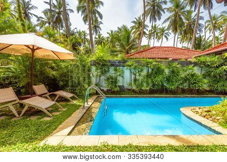 Pool With Umbrella And Beach Beds In Tropical Hotel Or House. Idyllic Scenic Courtyard. Scenery Of N