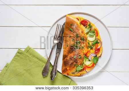 Omelette With Zucchini, Lamb's Lettuce, Tomatoes And Red Pepper On White Plate. Frittata - Italian O