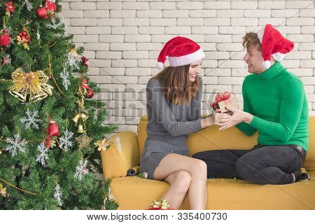 A Young Caucasian Couple Celebrating Christmas Together. The Man Gave His Girlfriend A Gift. It Was