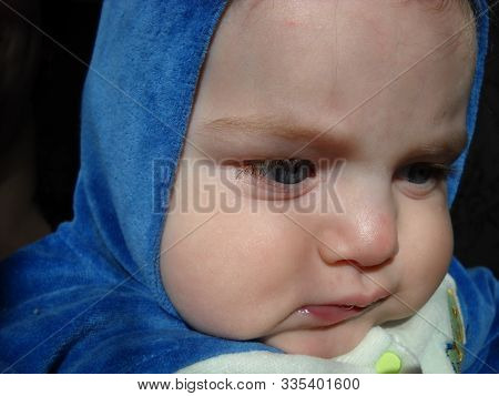 A Small Child Frowns And Eyebrows. A Look To The Side. On The Boys Head Is A Hood Of Blue Plush Over
