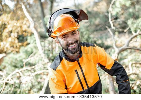 Portrait of a cheerful lumberman in protective workwear resting after the hard work in the forest poster