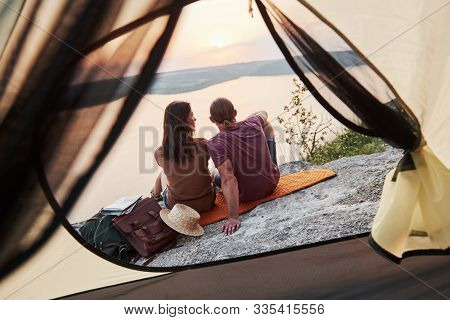 Photo Of Happy Couple Sitting Near Tent With A View Of Lake During Hiking Trip. Travel Lifestyle Adv
