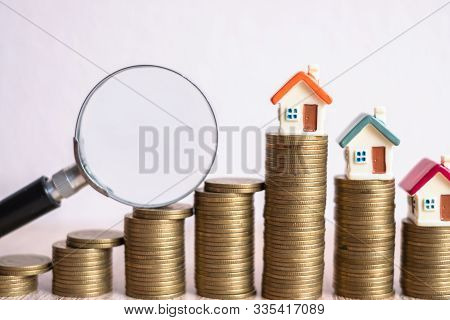 Miniature Of House With Magnifying Glass And Coin. House And Money. Toy House, Magnifying Glass And
