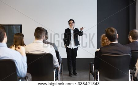 Business Training. Female Speaker Giving Lecture To Audience In Boardroom