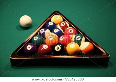 Sports Game Of Billiards On A Green Cloth. Multi-colored Billiard Balls In A Wooden Triangle With Nu