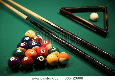 Sports Game Of Billiards On A Green Cloth. Multi-colored Billiard Balls In The Form Of A Triangle Wi