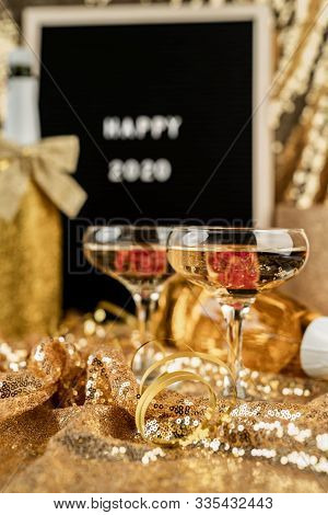 New Year Concept. New Years Eve Golden Party Table With Two Champagne Flute, Black Felt Letter Board