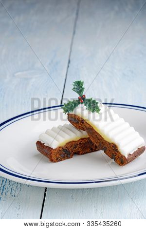Closeup Fruitcake With Holly On White And Blue Plate