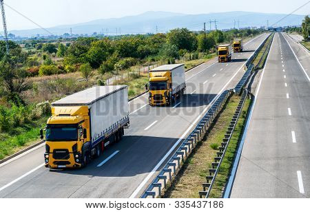 Caravan Or Convoy Of Four Yellow Lorry Lorry Trucks In Line On A Country Highway Under A Beautiful S